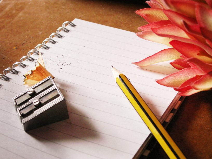 notebook with pencil, pencil sharpener and flower