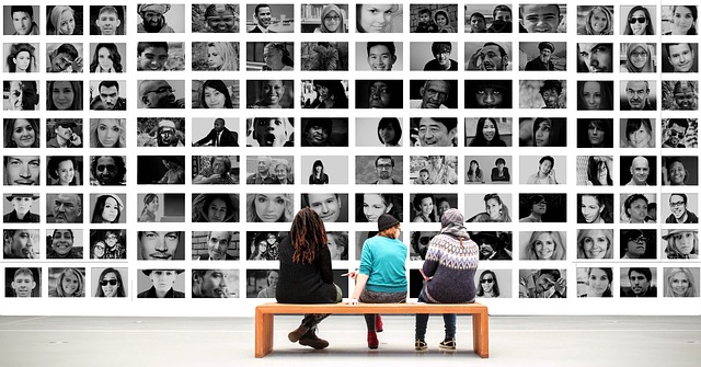 Three people sit on a bench observing a wall of photographs of faces