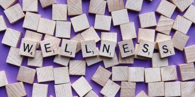 "A group of blank tiles against a purple background lie underneath eight marked tiles that spell out the word ""wellness."""