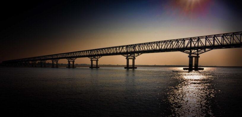 Photo of a bridge spanning a river at sundown